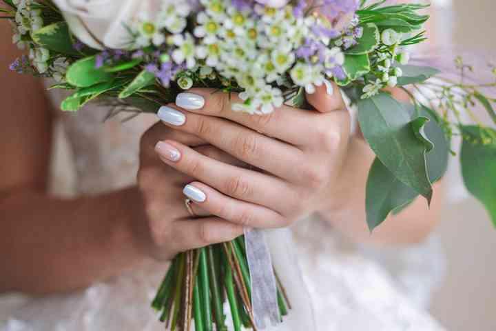 Manos sostienen ramo de novia con manicure