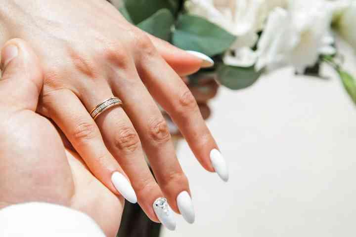 mano de novia con anillo de compromiso y manicure