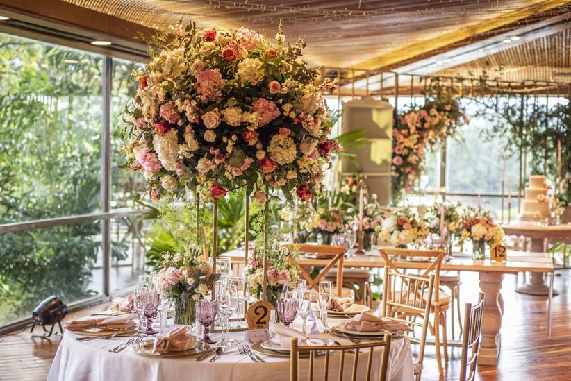salón de fiesta de boda con centros de mesa altos adornados con flores