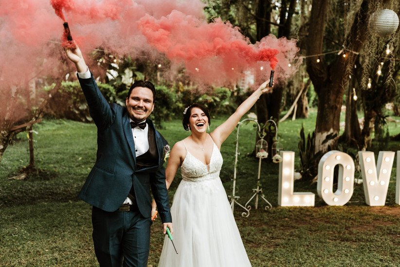 pareja de recién casados con bombas de humo de color en la recepción de matrimonio