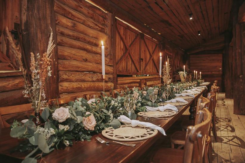 recepción de matrimonio de estilo rústico con centros de mesa con rosas y plantas