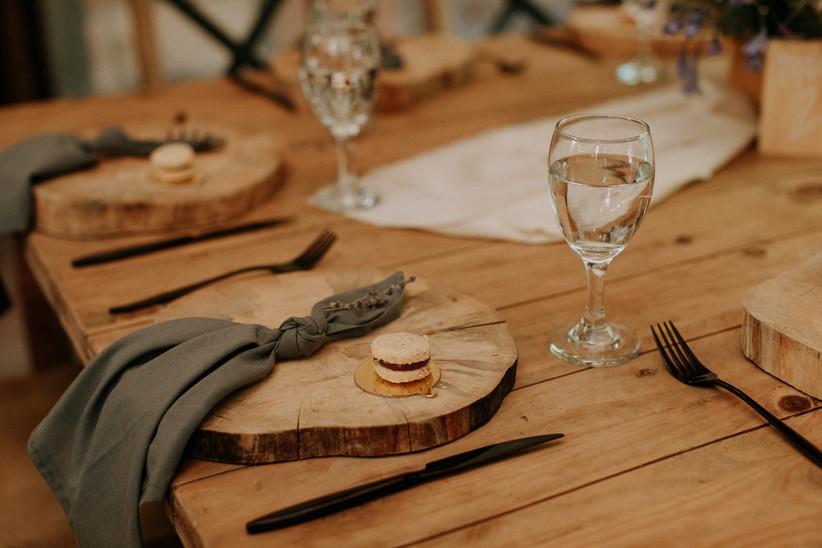 mesa de boda con individual de madera y servilleta verde con detalle de macaron para invitados