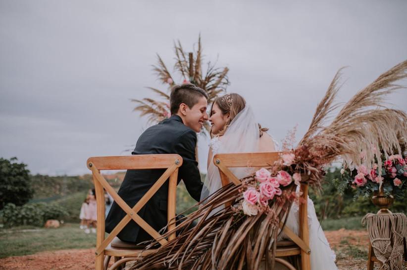 mesa de novios con sillas decoradas rústicas con flores