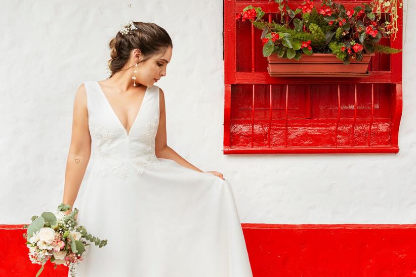 novia luce vestido de novia con escote en V y su ramo de flores