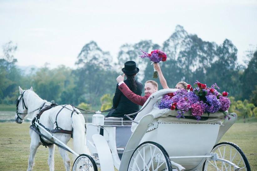 carroza con novios en la salida de boda