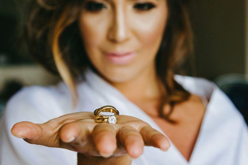 Novia con argolla de matrimonio y anillo de compromiso en mano